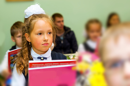 Little first-grader, girl-student in school on knowledge day - 1. September. Student of elementary school in uniform with bows posing in classroom for student Desk. Education in Russia Stock Photo
