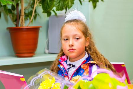 žák: Malý první grader, studentka ve škole v den znalostí - 1. září. Student základní školy v uniformě s luky představující ve třídě pro studentské stůl. Vzdělávání v Rusku