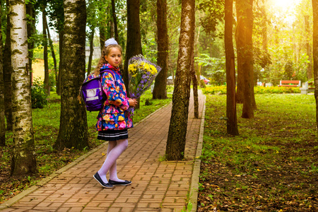Little first-grader, girl-student goes to school on knowledge day - September First. Student of elementary school in uniform with bow posing in autumn landscape. Shoulders bag with textbooks. Russia