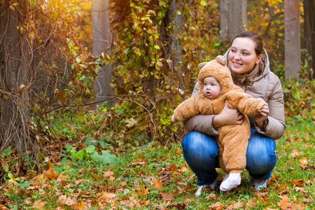 Woman with baby in arms, posing on background of autumn Park.Child dressed in warm stylized Teddy-bear costume, having fun on mothers arms. Family walk in Park Serhiivka, Peterhof, Petersburg Russia