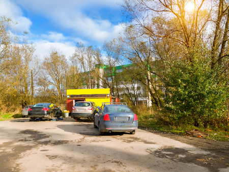 Modern cars are queuing on the tire service. Seasonal tyre replacement. Autumn in Krasnoe Selo. Saint-Petersburg, Russia