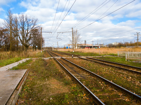 Railway station Krasnoe Selo in autumn. Passenger platform for boarding a suburban train RZD. Transport infrastructure-rail and high-voltage wires. Saint-Petersburg, Russia