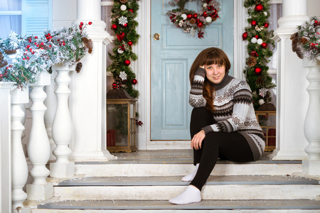 Beautiful young girl in a warm knitted sweater in cozy home, decorated entrance to house in bright colours with fir branches. Waiting for New year and Christmas