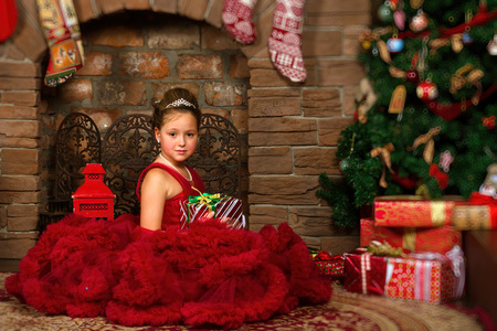 Little winter Princess, girl in red dress, sitting by fireplace, looking at box with gift. Celebration of New year and Christmas in enchanting holiday interior with decorated pine