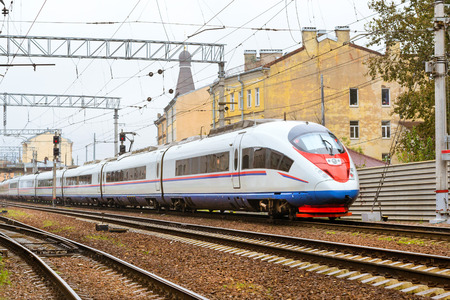 Modern hybrid electric locomotive Sapsan pulling a high-speed train on rails. Technical railway depot. Transport route Saint-Petersburg - Moscow, Russia