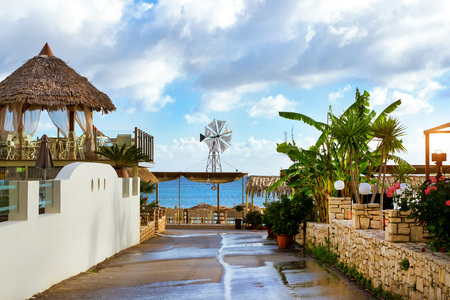Decorative windmill with white propeller installed on thatched roof. Tables with thatched umbrellas at beach cafe on seafront. Livadi beach in sea bay of resort village Bali. Crete, Greece