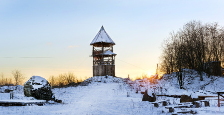 Wooden lookout tower stands on a snowy mountain. Winter landscape at sunset. Decorations of old Russian fortifications in Funny Nicholas Fortress Stock Photo