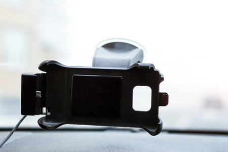 Car smartphone holder attached to the windscreen of automobile. Accessories for vehicles, for ease of control a car in the way. Phone holder with charging function