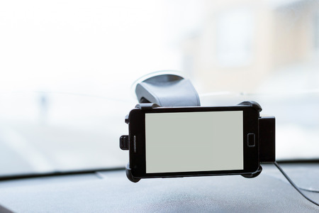 Car smartphone holder with phone attached to the windscreen of automobile. Accessories for vehicles, for ease of control a car in the way. Phone holder with charging function
