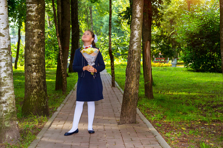 Little first-grader, girl student goes to school on knowledge day 1. September. Student of elementary school in uniform with flowers posing in autumn landscape. Teen goes to school, Russia