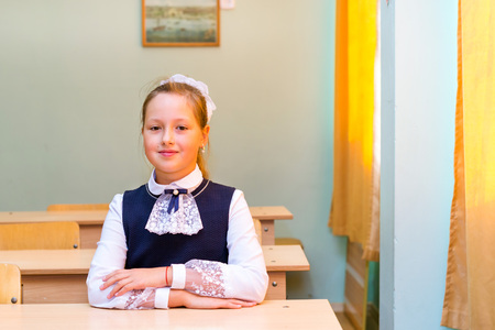 Little first-grader, girl-student in school on knowledge day - 1. September. Student of elementary school in uniform with bows posing in classroom. Education in Russia