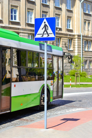 Passenger bus drives past the sign crosswalk on Central cobblestone paved road in Bialystok, Poland. Comfortable urban public transport and developed road infrastructure in Eastern Europe