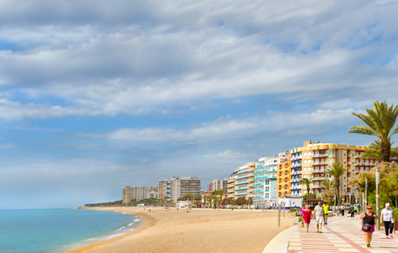 Blanes, Spain - 30 may, 2018: Coast of sandy beach and architecture of Spanish beach resort Blanes in summertime. Costa Brava, Catalonia. Tourists relax on beach and walk along the coastal promenade