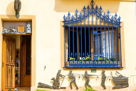 Blanes, Spain - 30 may, 2018: Architecture of Spanish beach resort Blanes in summertime. Costa Brava, Catalonia. Window with wrought bars and tin figures of fishermen on the wall Editorial