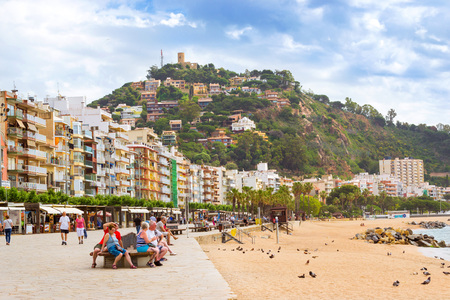 Blanes, Spain - 30 may, 2018: Coast of sandy beach and architecture of Spanish beach resort Blanes in summertime. Costa Brava, Catalonia. View on mountain of castle San Juan and Chapel of John Baptist
