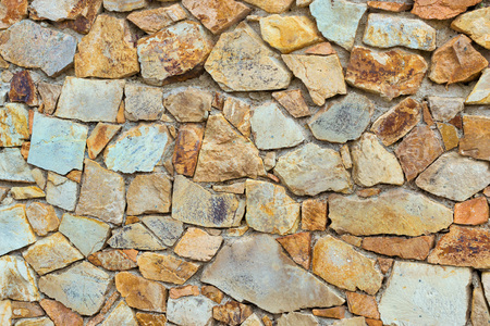 Decorative stone wall, pieces of rock bonded with cement. Cobble texture with cracks. Mountain of castle San Juan. Spanish beach resort Blanes in summertime, Costa Brava, Catalonia, Spain