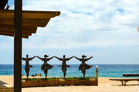 Blanes, Spain - 30 may, 2018: Monument to Sardana. Sculptural composition with dancing people. Sea with a sandy beach. Architecture of Spanish beach resort Blanes in summertime. Costa Brava, Catalonia