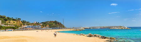 Blanes, Spain - 30 may, 2018: Coast of sandy beach and architecture of Spanish beach resort Blanes in summertime. Costa Brava, Catalonia. View on seaport