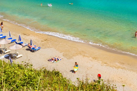 Bali, Greece - May 4, 2016: Sandy beach Varkotopos in sea bay of resort village Bali. Views of shore, washed by waves with sun loungers and parasols where sunbathing and swim tourists. Crete, Greece Editorial