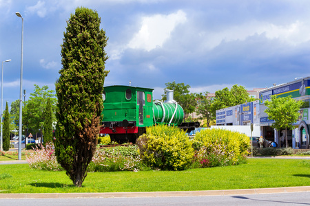 Blanes, Spain - 31 may, 2018: Monument to old locomotive on a pedestal among flower beds. Green retro train. Spanish beach resort Blanes in summertime. Costa Brava, Catalonia Editorial