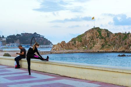 Blanes, Spain - 30 may, 2018: Athlete girl warming up before Jogging on promenade, Rock Sa Palomera. Coast of sandy beach, Spanish beach resort Blanes in summertime. Costa Brava, Catalonia Editorial