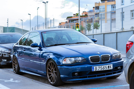 Blanes, Spain - 30 may, 2018: Blue modern coupe-car BMW 5-series E39 parked on street, in front of traffic lights. Architecture of Spanish beach resort Blanes in summertime. Costa Brava, Catalonia