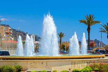 Blanes, Spain - 31 may, 2018: Round fountain among the road junction. Water jets hit up. Architecture of Spanish beach resort Blanes in summertime. Costa Brava, Catalonia. Flower bed in city square Editorial