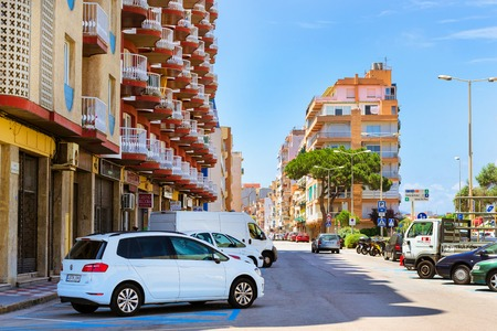 Blanes, Spain - 31 may, 2018: Coastal street of resort town with parked cars. National architecture of Spanish resort in summer. Buildings of hotels, apartments, cafes and restaurants are lit by sun