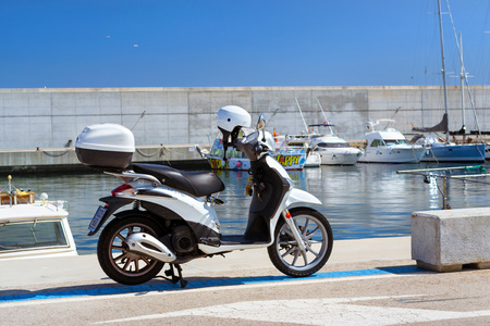 Blanes, Spain - 31 may, 2018: White scooter Liberty parked at pier in port Blanes. Fishing boats and yachts moored. Modern stylish city motor scooter. Costa Brava, Catalonia Editorial