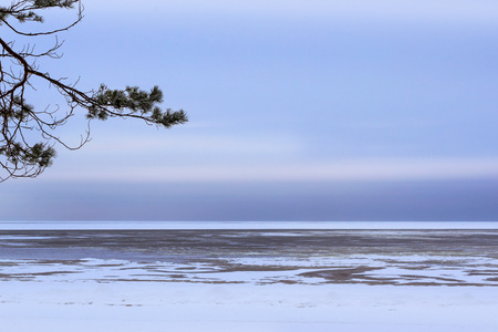 Winter day on snowy shore of Narva Bay. Snow on the ice of the frozen Gulf of Finland. Narva-Joesuu resort town in North-East of Estonia in Ida-Virumaa County. Severe Northern winter and snowy weather
