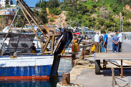 Blanes, Spain - 31 may, 2018: Fishing boats and yachts moored at pier in port Blanes. Fishermen unload catch of sea fish, oysters, squid, sea delicacies. Fish auction for wholesalers and restaurants