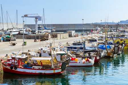 Blanes, Spain - 31 may, 2018: Fishing boats and yachts moored at pier in port Blanes. Fishermen unload catch of sea fish delicacies. Boats are moored to pier by ropes. Fish auction for wholesalers