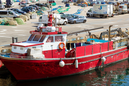 Blanes, Spain - 31 may, 2018: Fishing boat moored at pier in port Blanes. Fishermen unload catch of sea fish delicacies. Boat is moored to pier by ropes. Fish auction for wholesalers