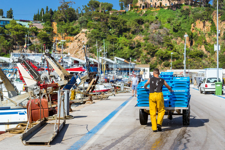 Blanes, Spain - 31 may, 2018: Fishermen unload catch of sea fish, oysters, squid, sea delicacies. Fishing boats and yachts moored at pier in port Blanes. Fish auction for wholesalers and restaurants Editorial
