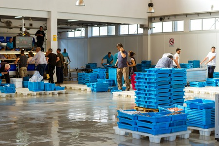 Blanes, Spain - 31 may, 2018: Buyers are traded at conveyor. Fish auction for wholesalers and restaurants. Blue plastic containers with catch of sea fish, ocean delicacies. Industrial catch of fish Editorial