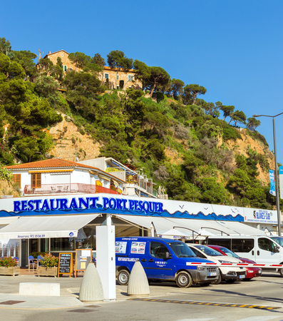 Blanes, Spain - 31 may, 2018: Restaurant Port Pesquer. Convent of Blanes on top of Punta Santa Anna. Architecture of Spanish beach resort Blanes in summertime. Costa Brava, Catalonia, Spain Editorial