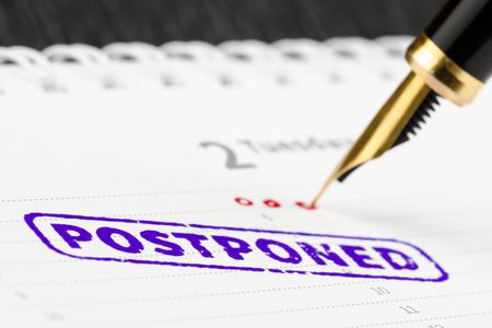 scheduler: Macro shot of postponed stamp and fountain pen on a scheduler.