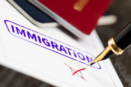 immigrants: Application form close up, fountain pen and immigration stamped on a document.