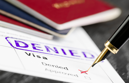 Visa form close up, fountain pen and denied stamped on a document.