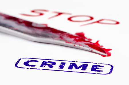 savagery: Macro shot of stamp crime on a white paper. Knife and stop written in blood.