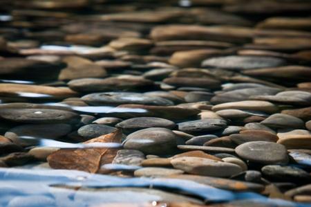 River Bed - Stenen onder het heldere water van een rivier Stockfoto