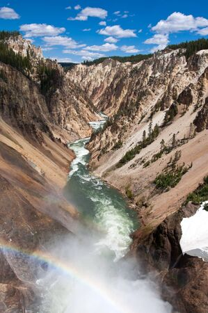 Double Rainbow in the mist of a waterfall in a canyon in Yellowstone National Park