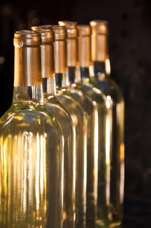 Closeup of bottles of white wine in a row fading into the distance Banco de Imagens