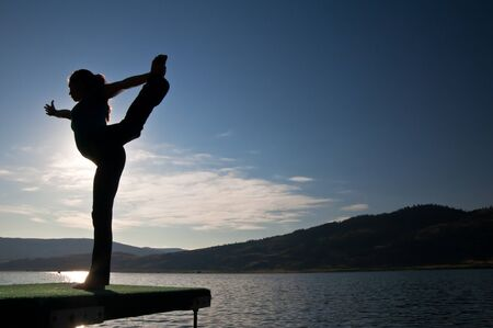 Silhouette of beautiful young girl doing a dancers pose by a lake Banco de Imagens