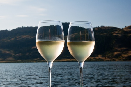 Closeup of two glasses of white wine with condensation on the outside of them next to a lake photo