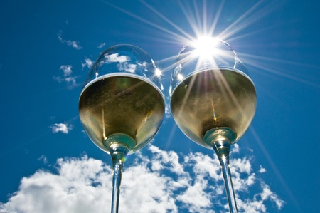 closeup of two wineglasses with a sun burst filled with white wine side by side with bright blue sky & clouds in the background Foto de archivo