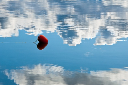 A buoy floating in the calm water of a lake with the reflection of the blue sky and clouds surrounding it Banco de Imagens