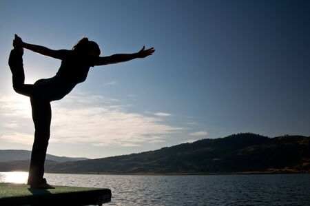 Silhouette of a beautiful young girl doing a dancers pose on the end of a dock by a lake