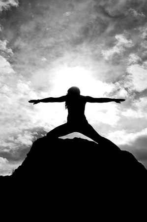 Black and white silhouette of a young attractive girl doing the Warriors pose from yoga on top of a rock with the sky and clouds behind her  Banco de Imagens