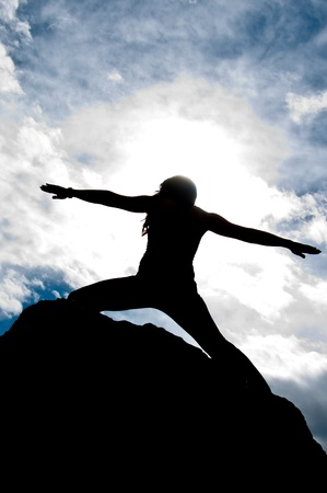 Silhouette of a young attractive girl doing the Warriors pose from yoga on top of a rock with the sky and clouds behind her  photo